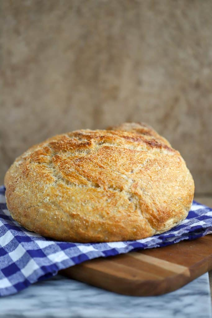 Knead Not Sourdough Bread or No Knead Sourdough Bread Recipe fresh bread on a blue checked cloth on a wooden cutting board