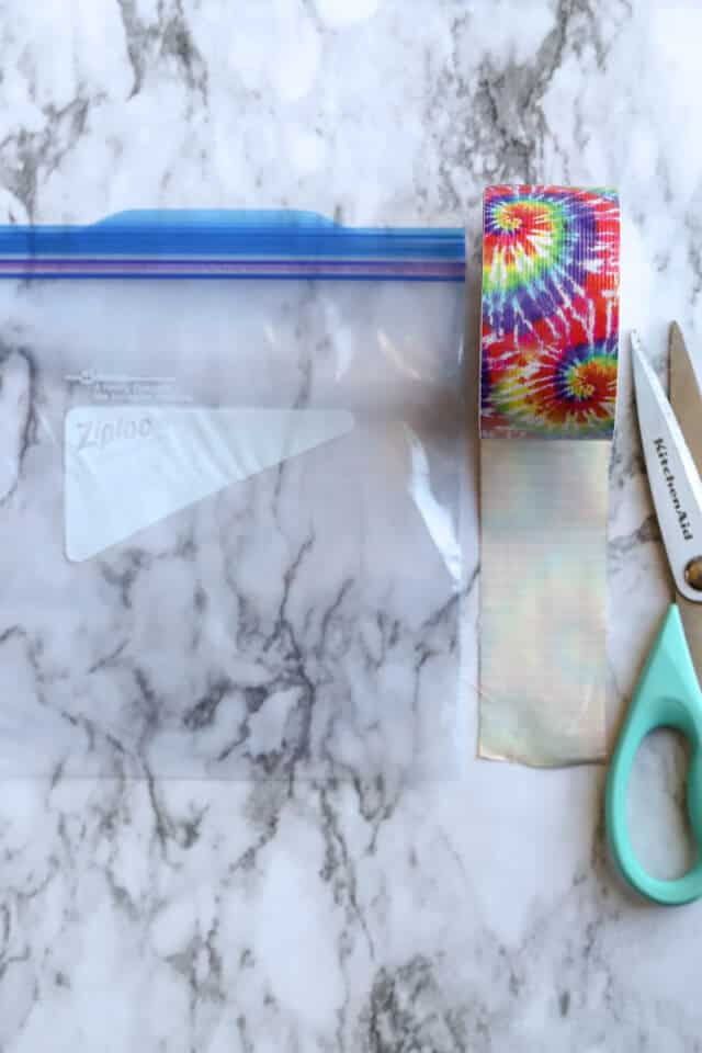 Ziploc Freezer Bag with duck tape and scissors on a marble countertop