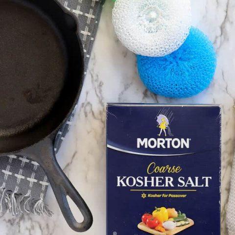 Cast iron pan with kosher salt and nylon scrub brush
