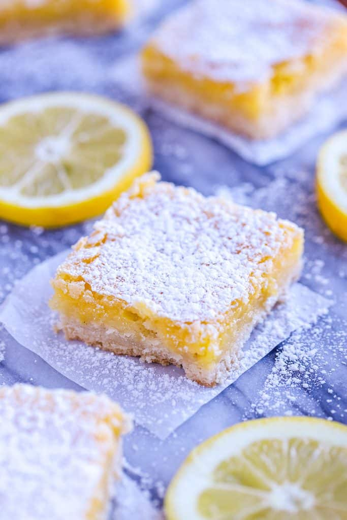 Lemon Square with lemon slices on parchment paper