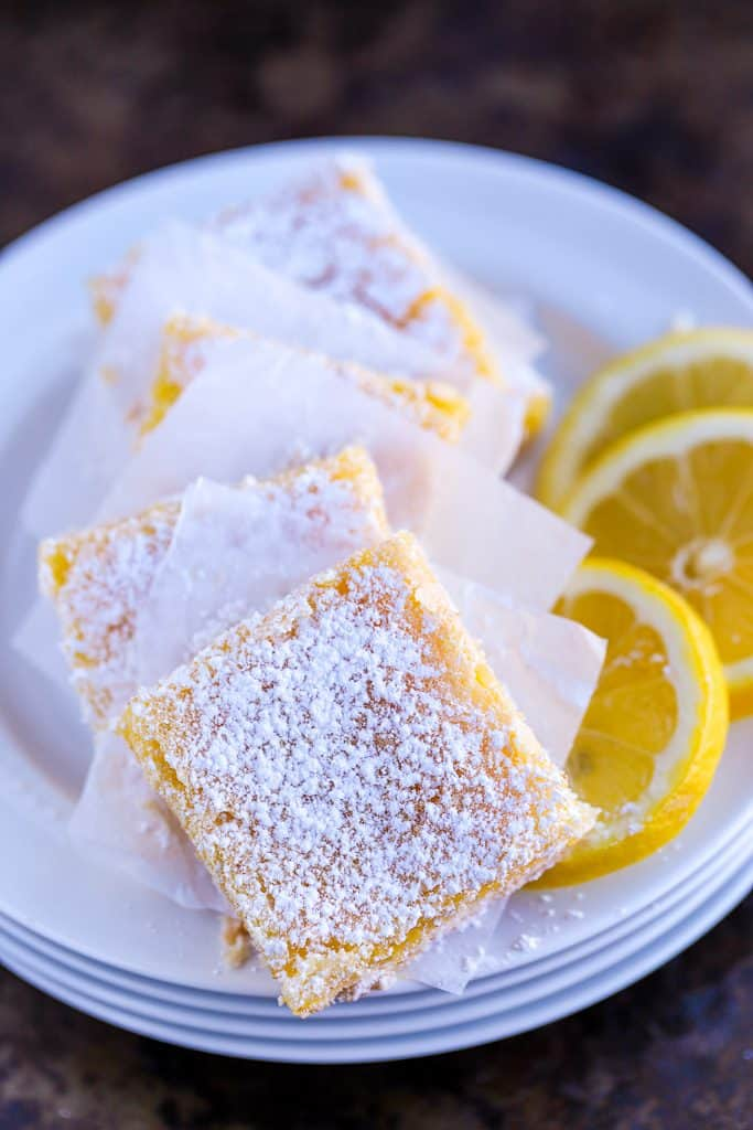 five Lemon squares on a plate with lemon slices