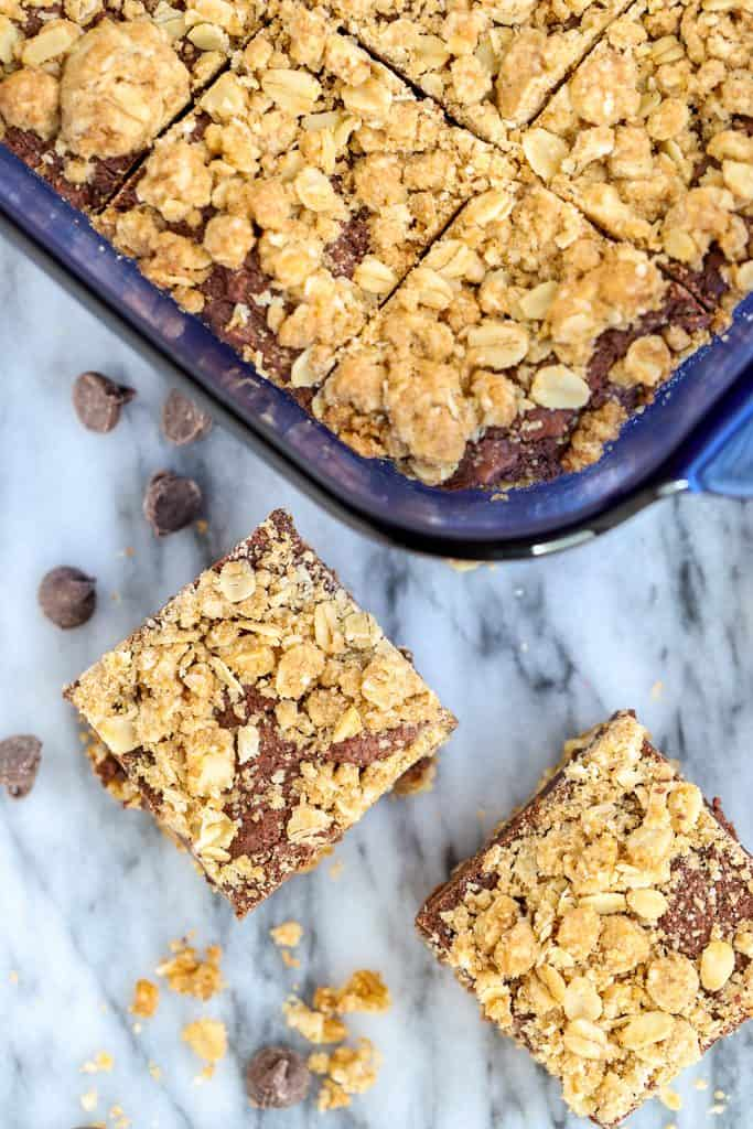 Overhead photo of oatmeal fudge bars with two individual squares next to the blue pan filled with more bars