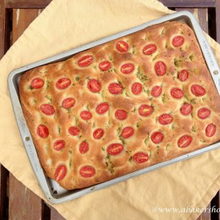 Overhead photo of cherry tomato focaccia on a baking sheet and yellow napkin
