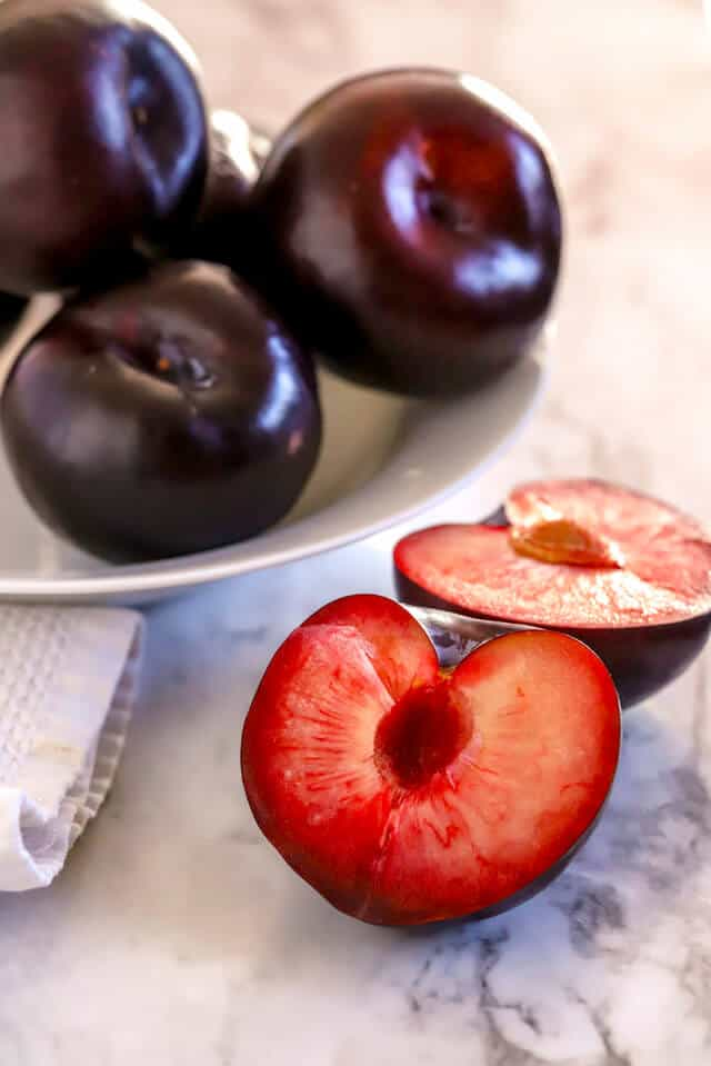 Plum cut in half with bowl of plums in background