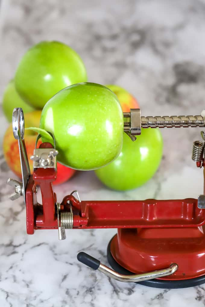 Apple peeler and corer device with granny smith apple ready to be peeled