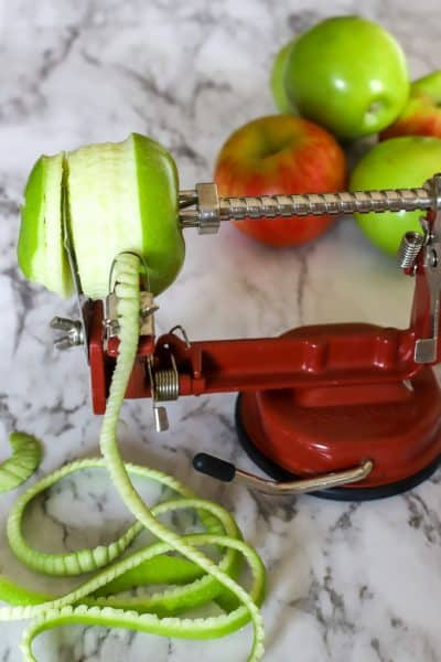 Apple peeling with apple corer and peeler with granny smith apple being peeled on a marble countertop