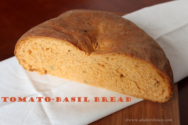 homemade tomato basil bread loaf cut in half on a white napkin