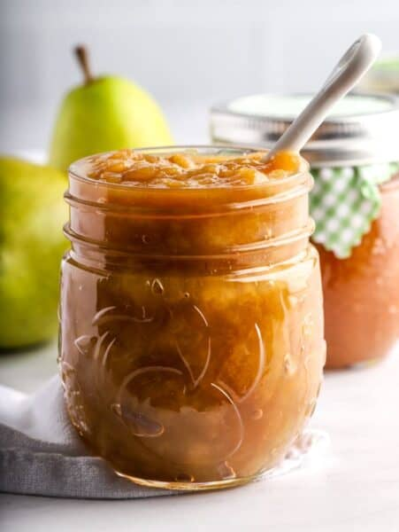 Pear ginger jam in a mason jar with white spoon