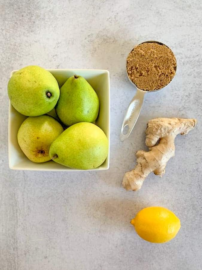 Ingredients for pear ginger jam of pears, sugar, ginger and lemon on a concrete tabletop