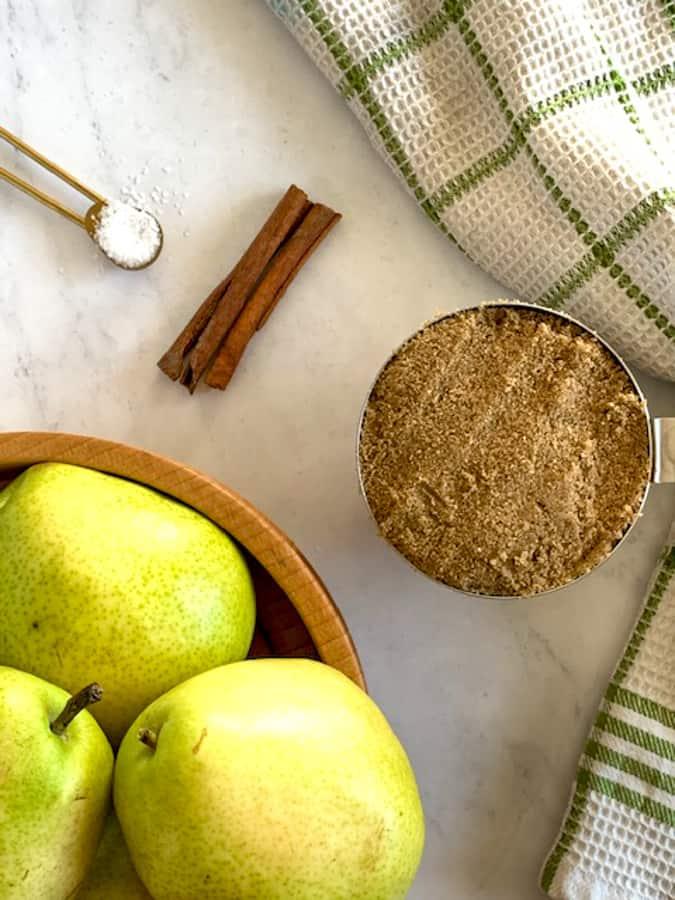 Ingredients of pear butter of pears, cinnamon, brown sugar and salt on marble board