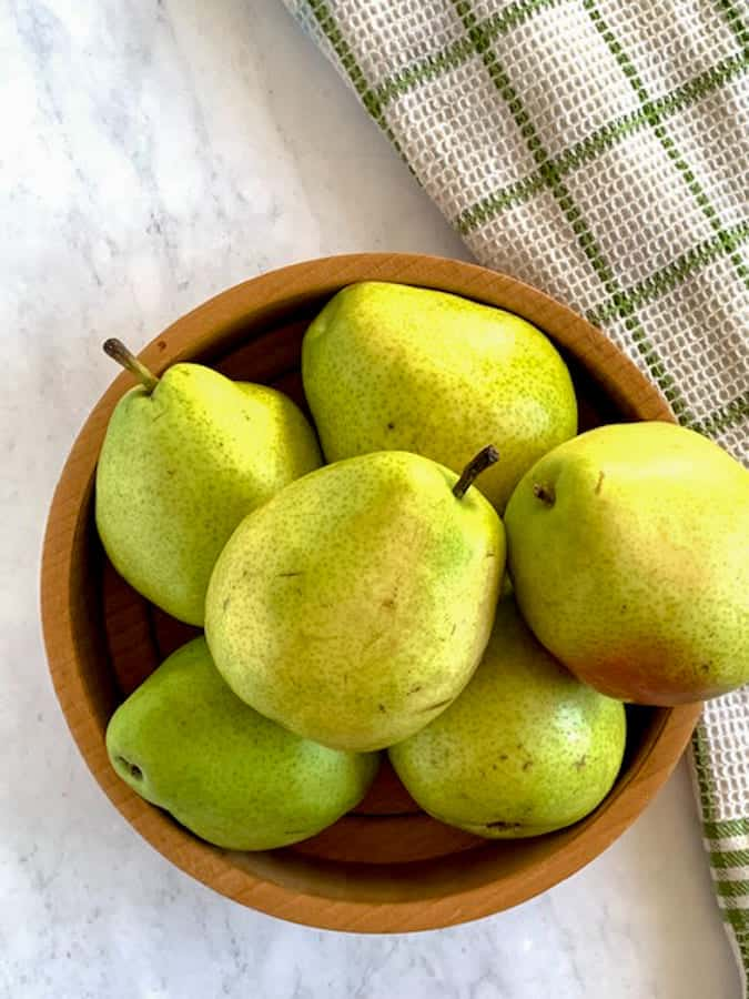 Pears in a wooden bowl on marble countertop