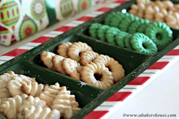 Christmas Spritz Cookies in the shape of trees and wreaths on a holiday serving tray