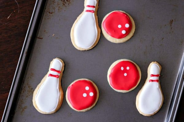 Cookies shaped like Bowling Ball and Pins on a metal baking sheet
