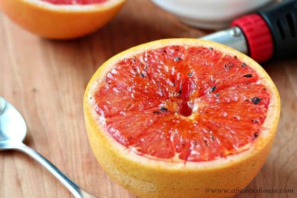 Bruleed grapefruit on a wood board with brulee torch in background