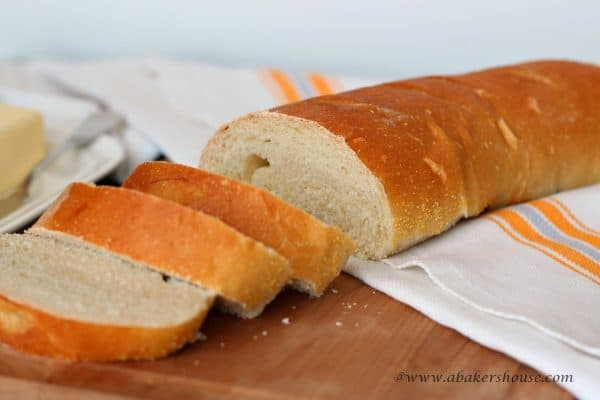 sliced loaf of French bread on wooden cutting board