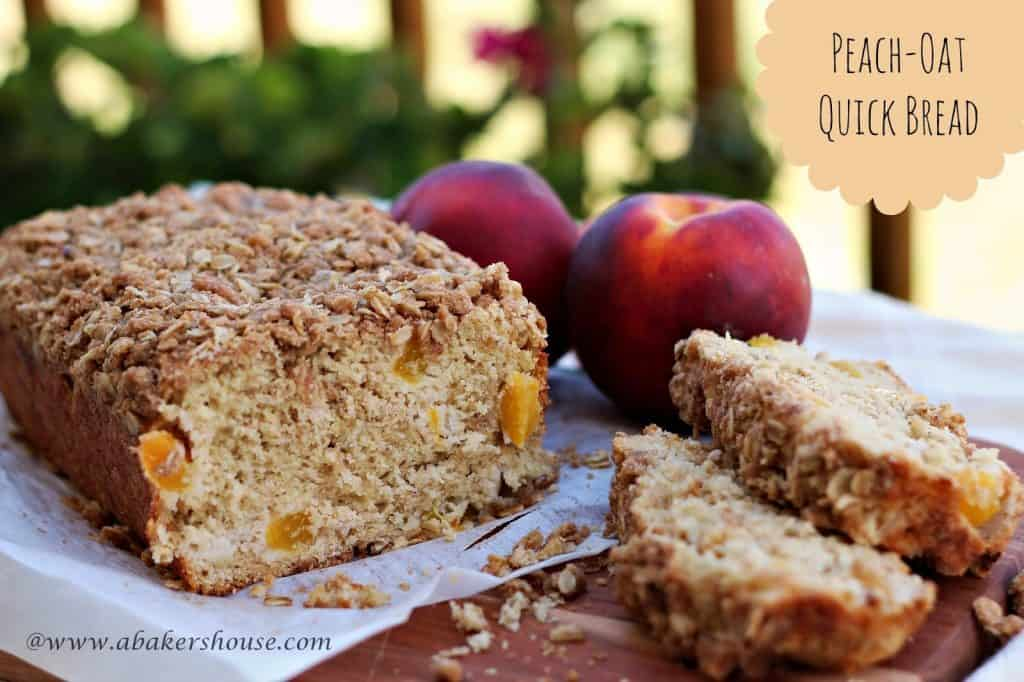 Peach oat quick bread with streusel topping sliced next to fresh peaches