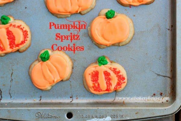 orange pumpkin decorated cookies on a gray baking pan