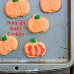 Pumpkin spritz cookies on a metal baking tray