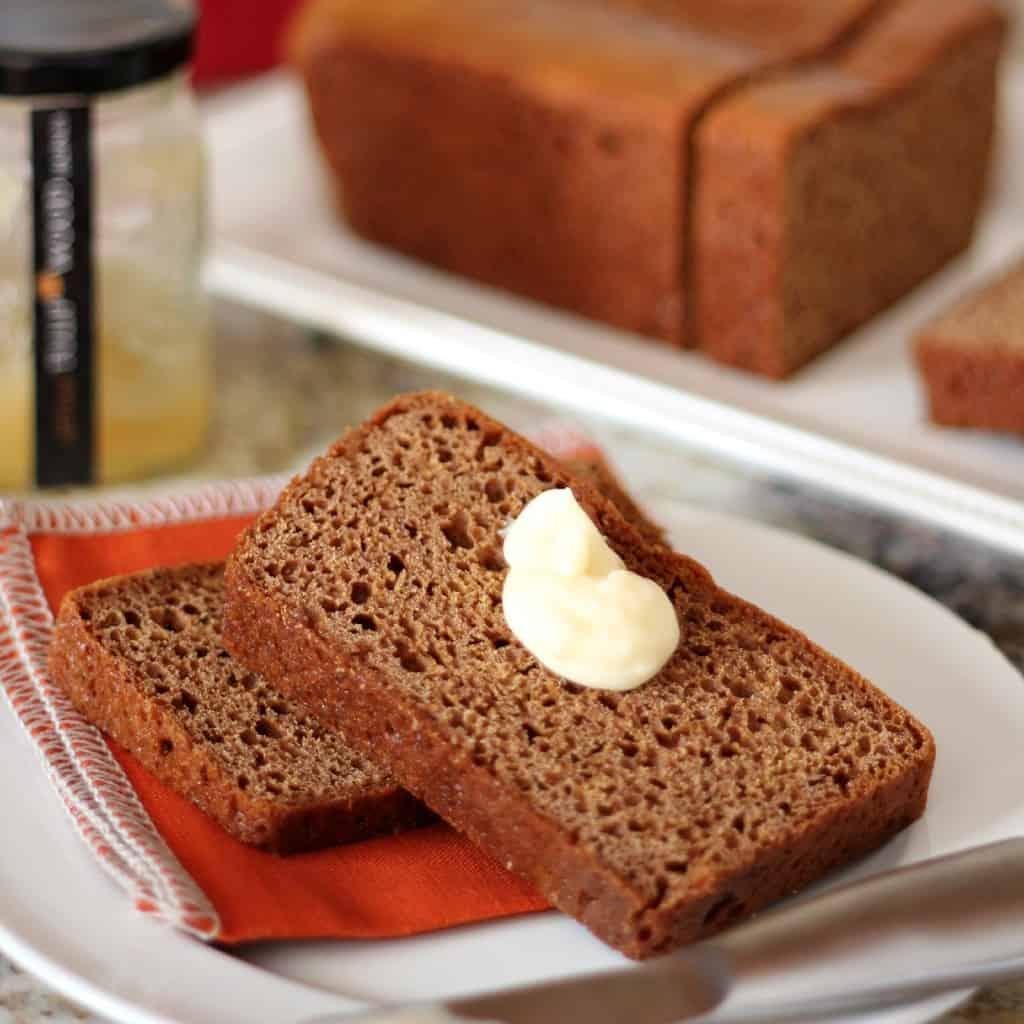 honey spice bread sliced on white plate with orange napkin