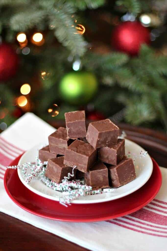 pile of cookie butter fudge on white plate and red plate with Christmas tree in background