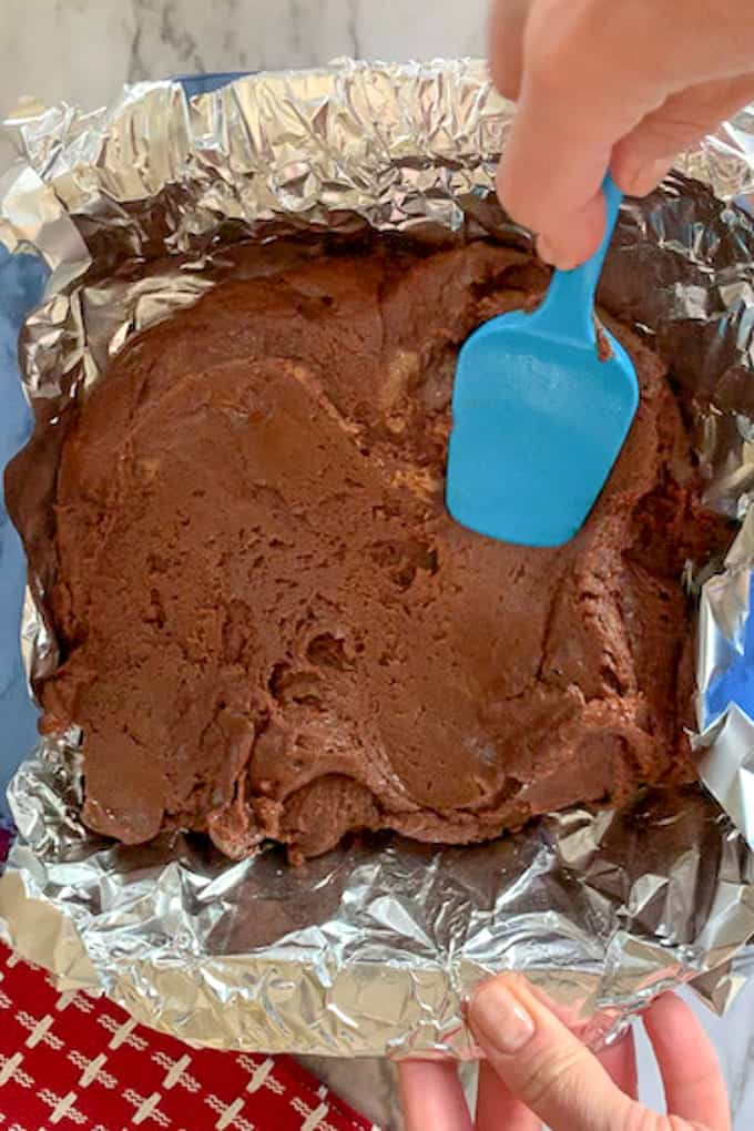blue spatula spreading the cookie butter fudge in aluminum foil baking pan