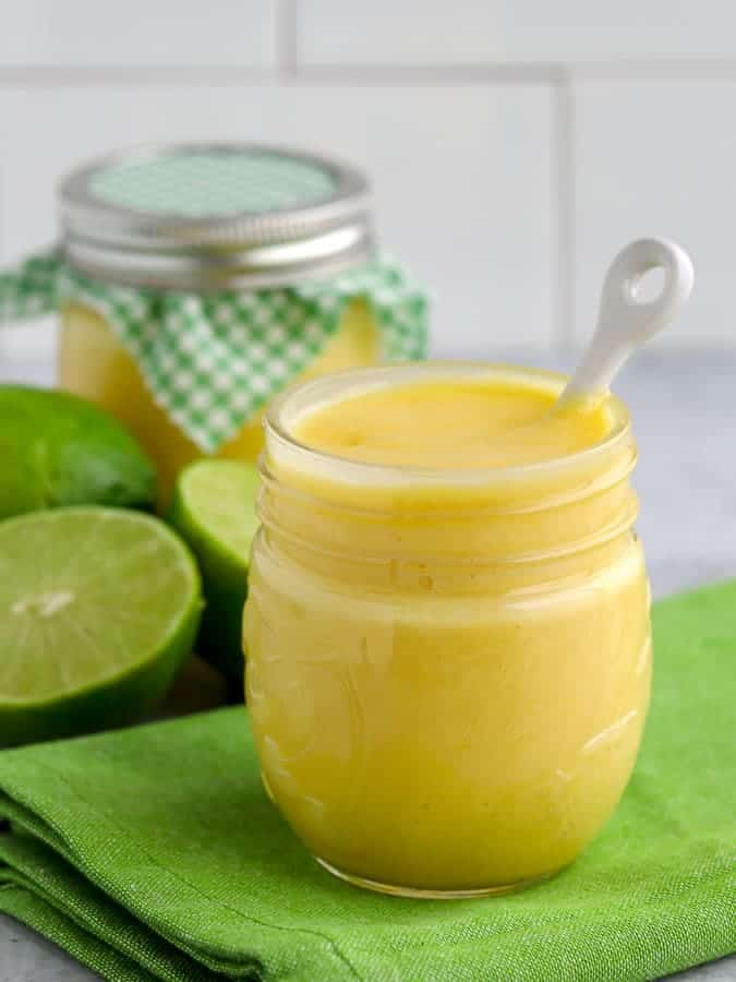 Two jars of lime curd with limes on green napkin