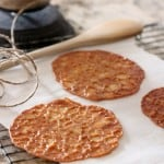 Almond lace florentines on a white parchment with wire baking rack