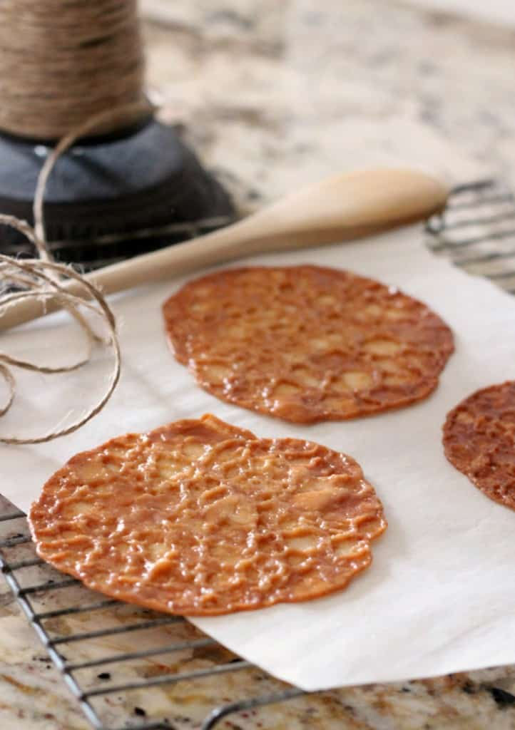 almond lace cookies on white parchment paper with wooden spoon and twine in background