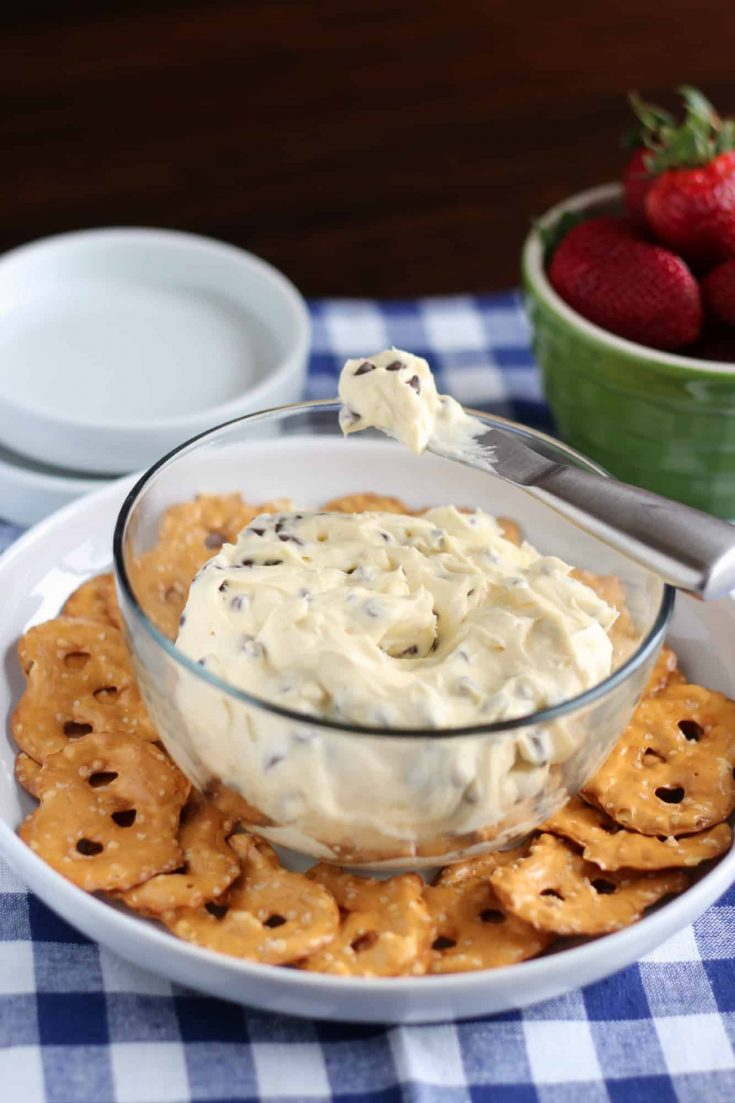 Chocolate Chip Cookie Dough Cheesecake Dip will be the star of the party. Creamy, sweet, and easy to make, this dip is everything you love about cheesecake but made in a matter of minutes #abakershouse #cheesecake #cookiedough #partydip