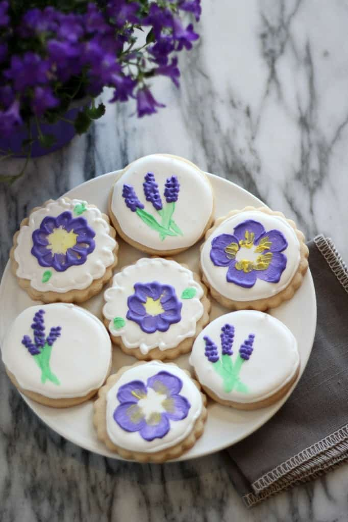 Sugar cookies decorated with painted flowers all on a plate