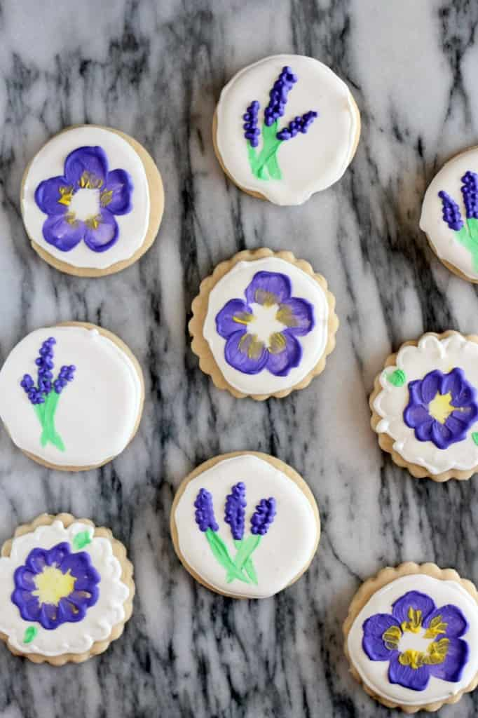 purple painted flower cookies on a marble tray