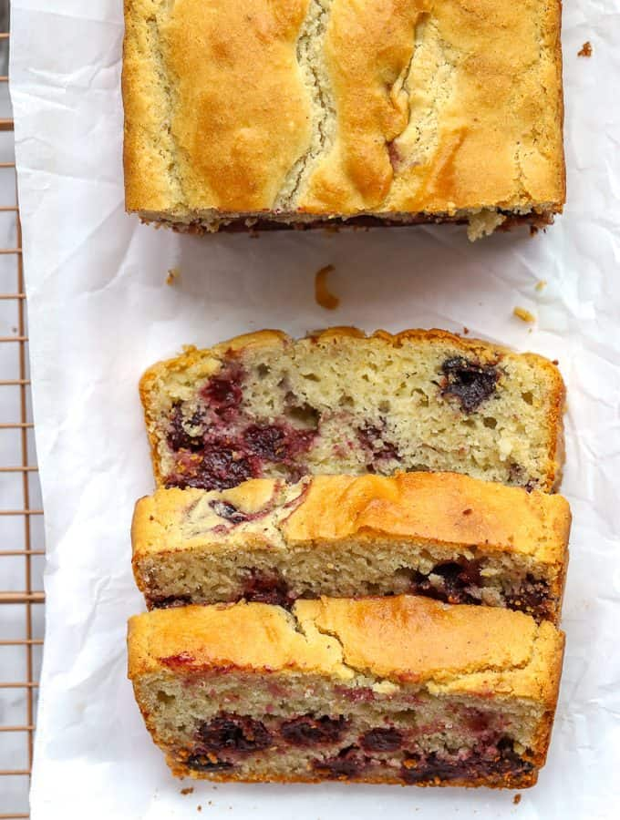 Overhead photo of gluten free cherry quick bread with three slices on white parchment