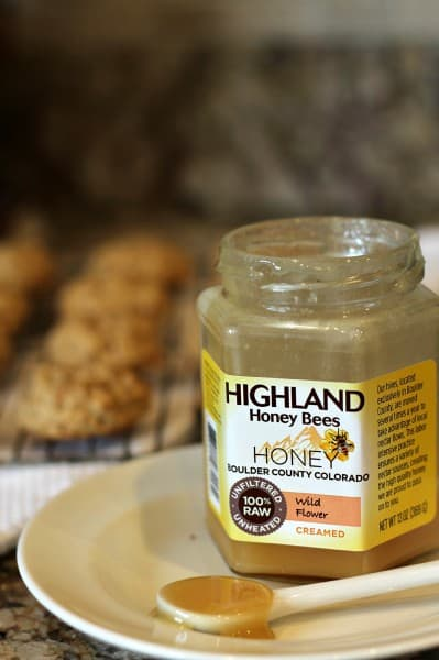 highland honey with spoonful on white plate and cookies in background