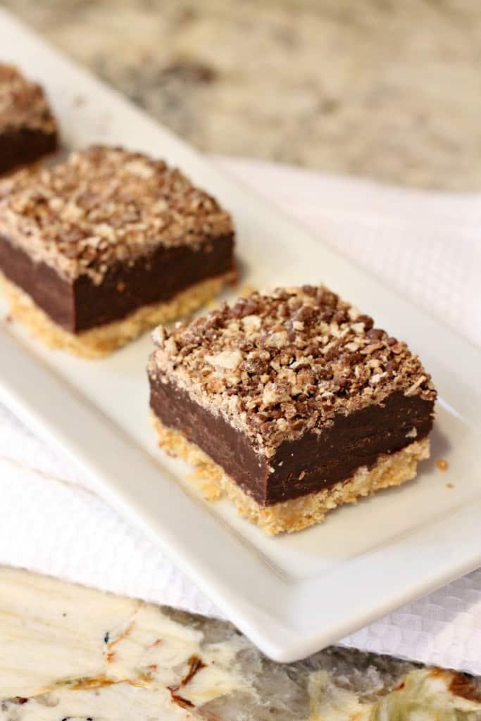 No bake kit kat squares on a white rectangular platter on a granite counter top