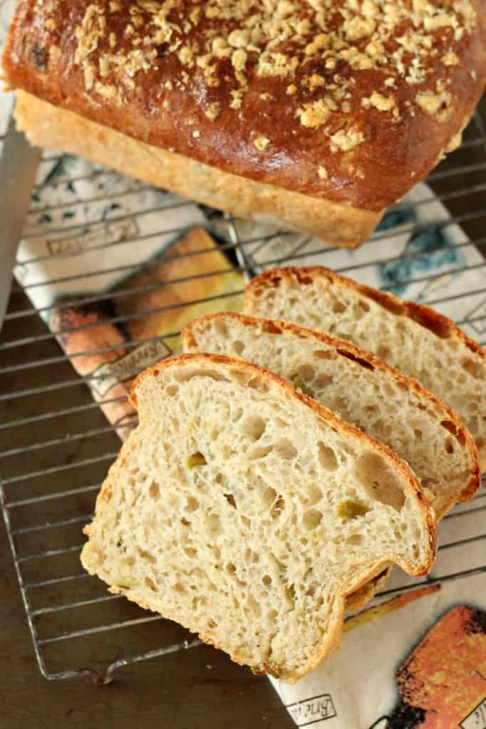 hatch chile bread sliced on baking rack with loaf in background