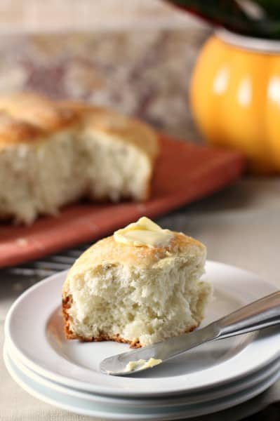 rosemary roll with butter on a white plate