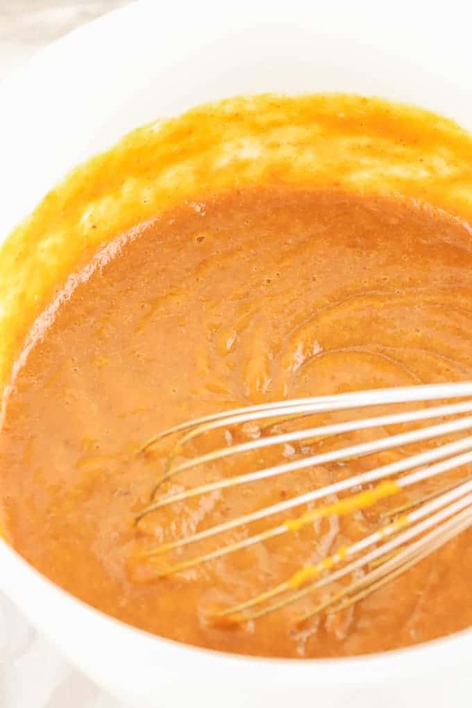 Whisk in a white bowl of ingredients with pumpkin puree for gluten free pumpkin pie filling