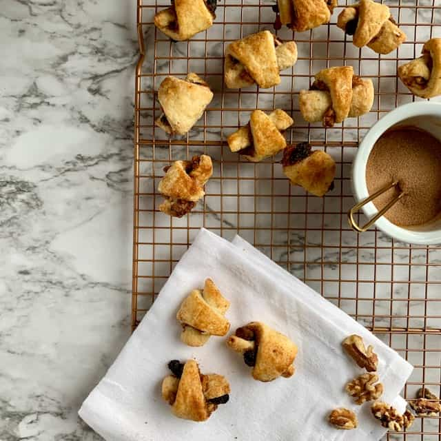 Baked rugelach on white napkin and more on cooling rack