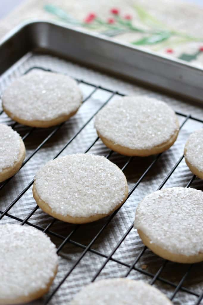 sugar cookies with sparking sugar on a cooling rack on a baking sheet