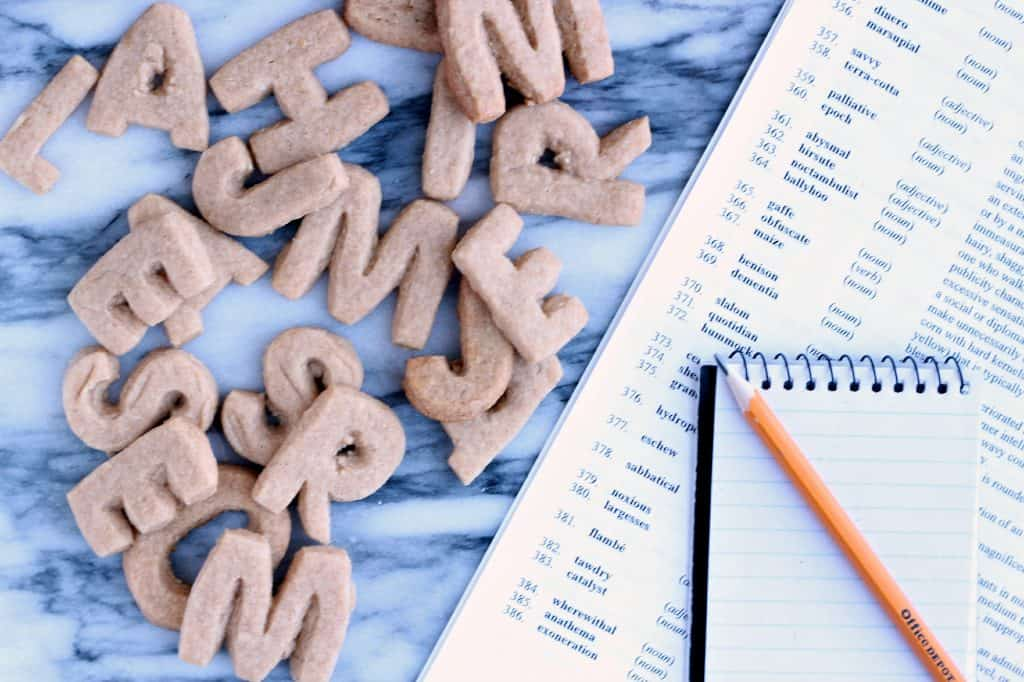 Alphabet letter cookies on a marble board with list of spelling bee words aside