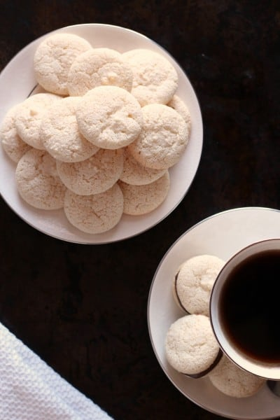 amaretti biscuits on a plate near a cup of coffee