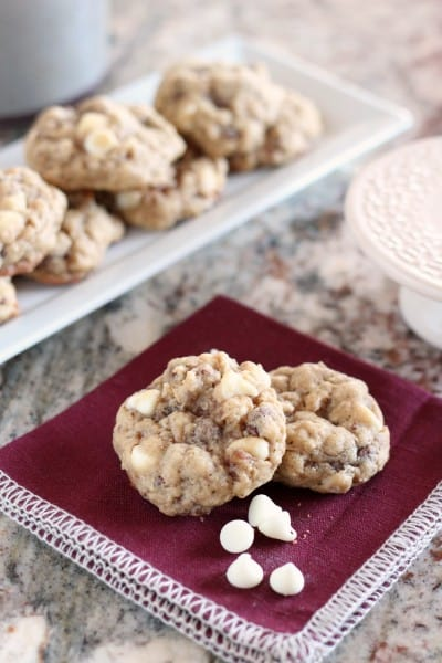 Two Oatmeal white chocolate cookies on dark napkin with a few white chocolate chips