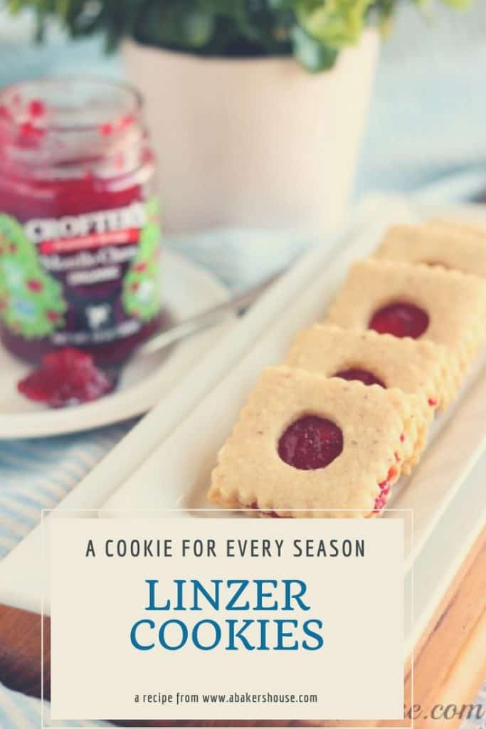Linzer Cookies on white rectangular platter with jar of jam