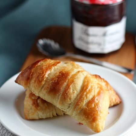homemade danish pastry on white plate with jam jar behind