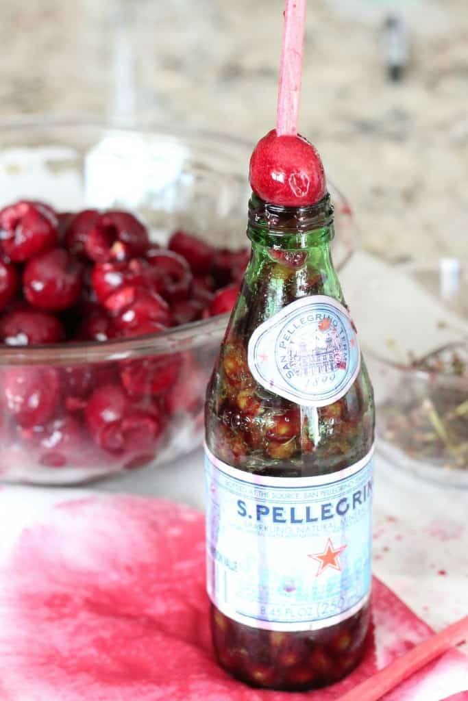 cherry set on top of glass bottle with chopstick used to take out the pit