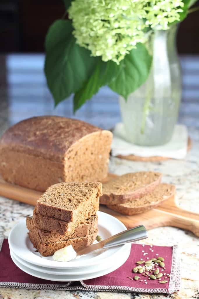 molasses seed bread sliced on a cutting board with flowers in background