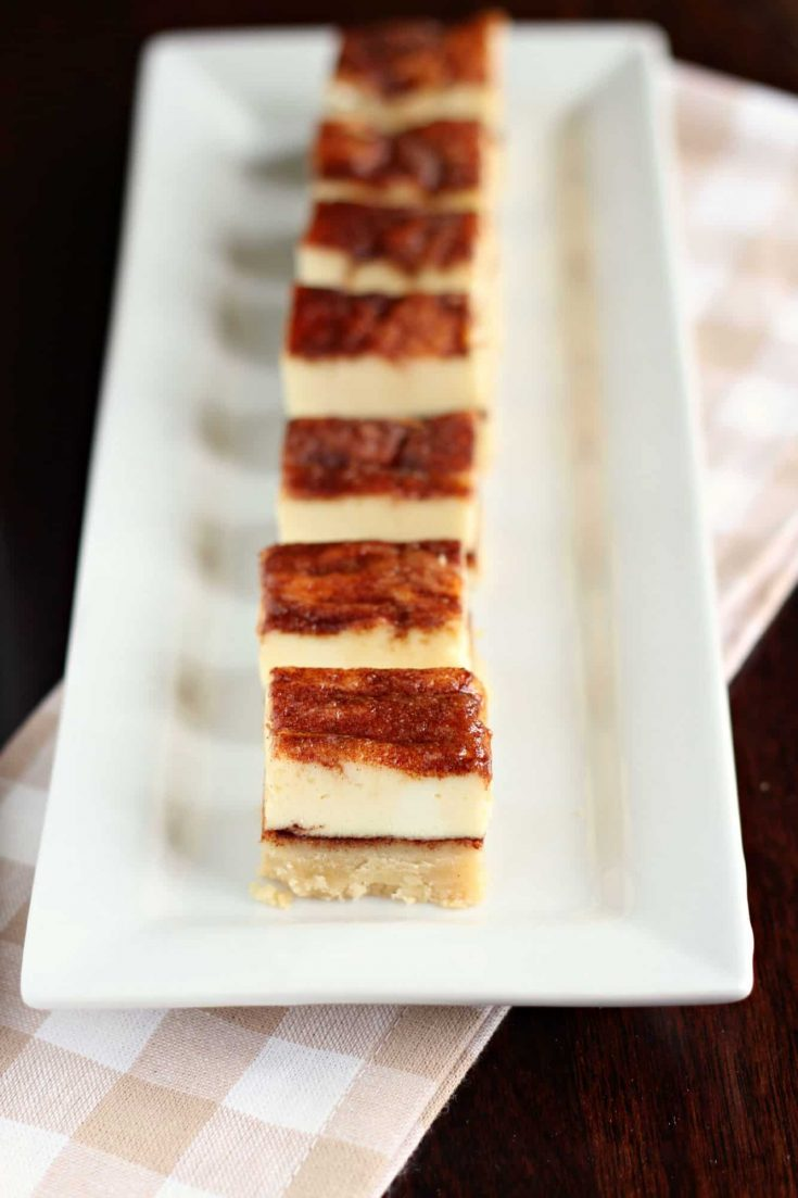 Churros cheesecake bars have a shortbread crust with a cheesecake filling. Bite-sized squares make this dessert easy to serve to a crowd. #abakershouse #churros #cheesecake #dessertbars #dessertsquares #cheesecakebars