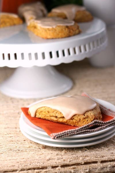 Pumpkin scone with glaze icing on white stack of plates