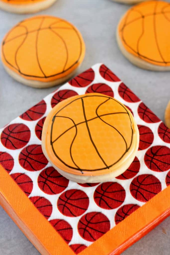 basketball cookie decorated with orange royal icing resting on a basketball napkin