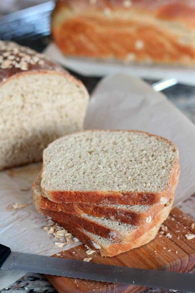 slices of maple oatmeal bread with loaf of bread in background